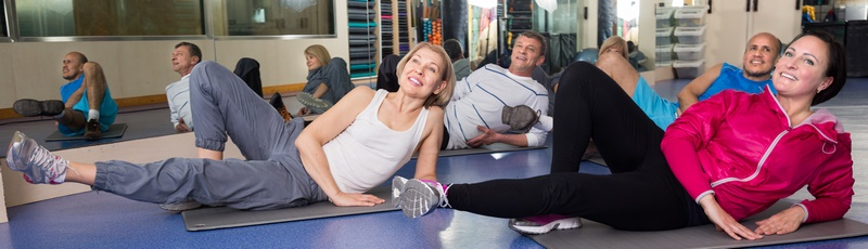 happy mature men and women are engaged on mat in gym. focus on the left woman